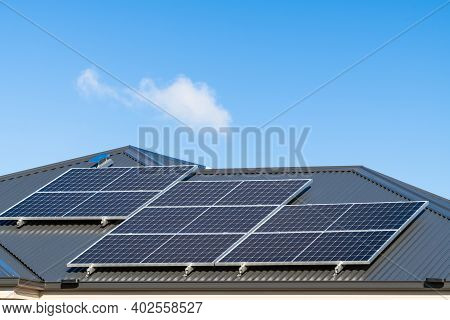 New Solar Panels Installed On Metal Sheet Roof Of The House In South Australia Againt Clear Blue Sky