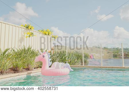Unicorn Inflatable Ring In Pool On Waterfront Home, Social Distancing During Coronavirus, Covid Lock