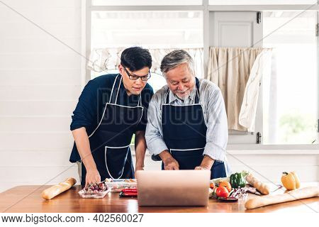 Portrait Of Happy Love Asian Family Senior Mature Father And Young Adult Son Having Fun Cooking Toge