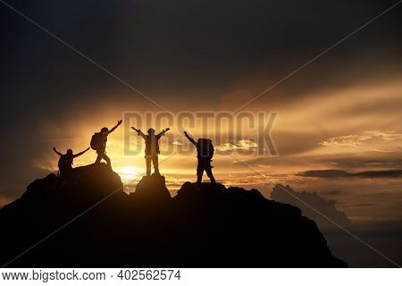 Silhouette Of Hikers Climbing Up Mountain Cliff. Climbing Group Helping Each Other While Climbing Up