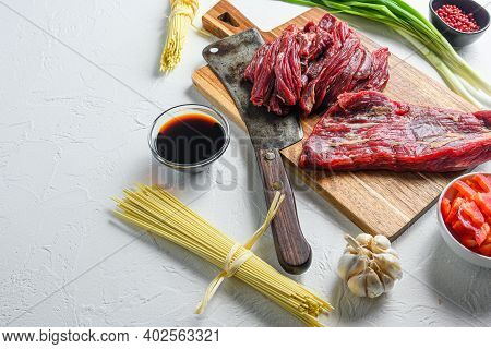Cooking Ingredients For Making Stir-fried Yakisoba With Beef. Side View On White Table With Space Fo