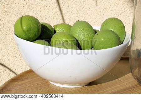 Bowl Filled With Limes Besides A Drinking Water Pot On An Outdoor Table At A Patio Taken In A Reside