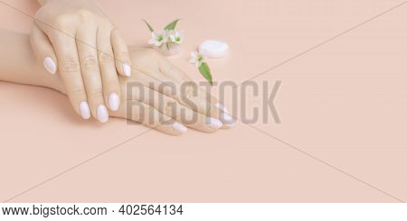 Beautiful Woman Hands With Flowers On Pink Background. Concept Hand Care, Anti-wrinkles, Anti-aging