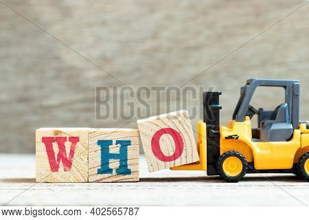 Toy Forklift Hold Letter Block O To Complete Word Who On Wood Background