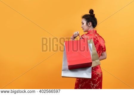 Beautiful Asia Girl Wear Cheongsam Hold Shopping Bags In Chinese New Year On Yellow Background.