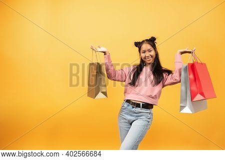 Asian Black Teenage Girl With Shopping Bags On Yellow Background. Shopaholic Shopping Fashion.