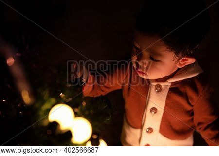 Little Boy Decorating Christmas Tree At Night In The Home