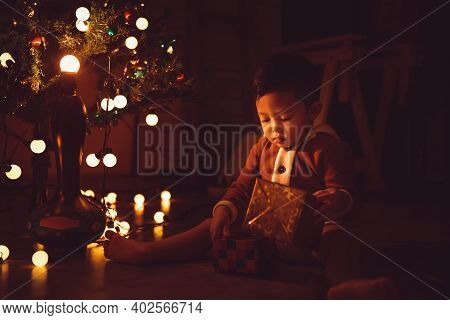 Little Boy Sitting Enjoy With Gift Box And Christmas Tree At Night In The Home