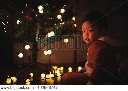 Little Boy Sitting Enjoy Near Christmas Tree At Night In The Home