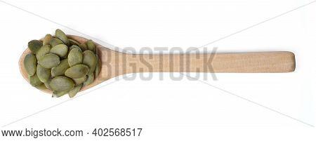 Isolated Pumpkin Seeds . Raw Pumpkin Seeds On Wood Spoon Organic Food  Ingredients On White Backgrou