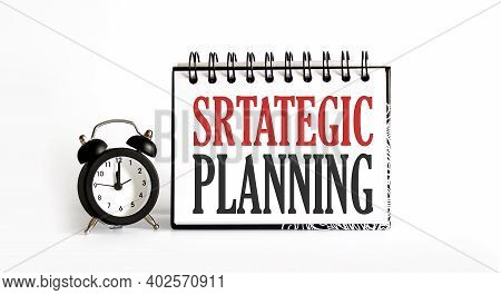 Strategic Planning Memo Written On Notebook With Alarm Clock