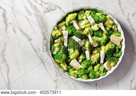 Steamed Broccoli Florets Prepared To Bake With Brie Cheese In A Baking Dish, Horizontal View From Ab