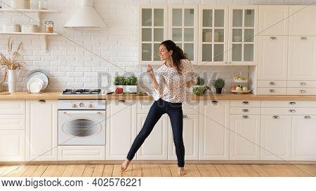 Happy Female Renter Enjoy Dancing In Home Kitchen