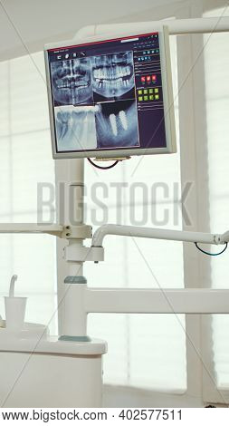 Pediatric Dentist Showing On Monitor Teeth X-ray Reviewing It With Mother And Daughter. Doctor And N