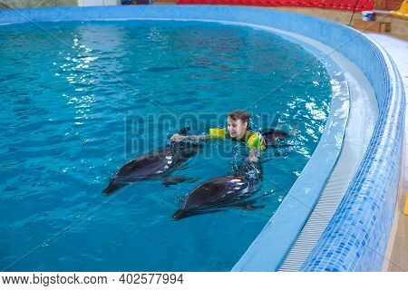Dolphin Therapy. Dolphins Swimming With Happy Little Girl In Dolphinarium. Swimming, Bathing And Com