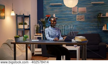 Young Smiling African Entrepreneur Woman With Headphones Sitting At Home Office Desk, Listening Musi