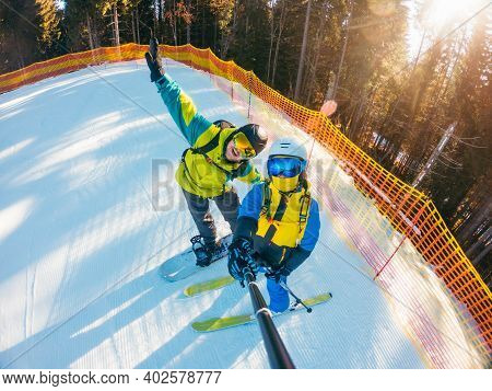 Couple Snowboarder And Skier Taking Selfie At Ski Slope