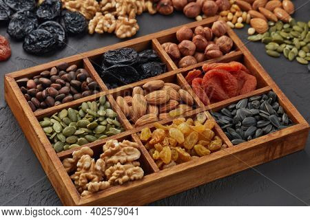 Various varieties of nuts, seeds and dried fruits lying in wooden box on black slate background. Top view. Healthy food. Vegetarian nutrition