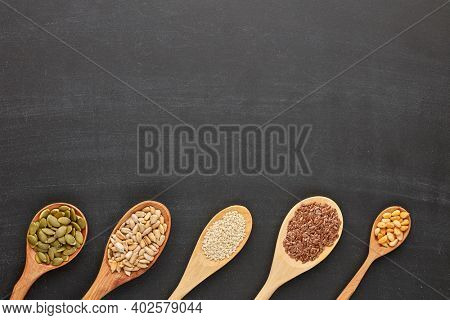 Various varieties of nuts and seeds lying in wooden spoones on black slate background. Top view with copy space. Healthy food. Vegetarian nutrition