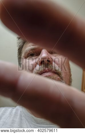 Confidence And Composure. Portrait Of An Adult Man Covering Himself From The Camera. Bottom Up View.