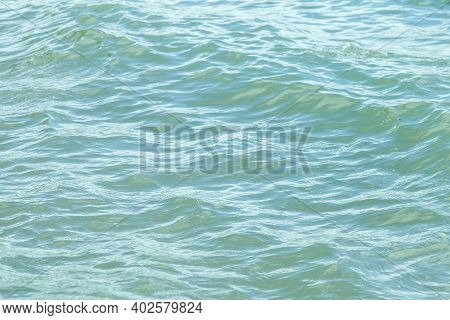 Close-up Of A River With Undulating Waves With Muddy Gray Water In Cloudy Weather. Background For Wa