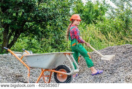 Kid Working On Construction Site. Teen Girl Takes Out Rubble From Wheelbarrow. Kid With Shovel Loadi