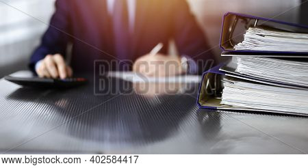 Binders With Papers Are Waiting To Be Processed By Unknown Man Accountant In Blue Blazer Staying At