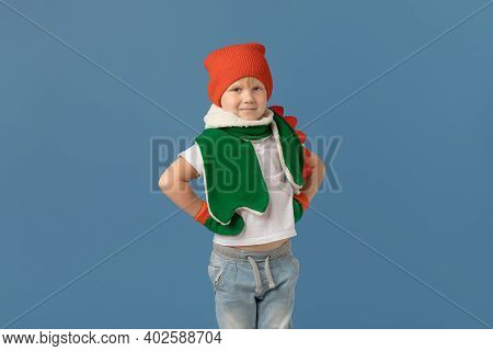 Boy Of European Appearance, Child In Red Hat And Green Scarf On Blue Background. Studio Shot About W