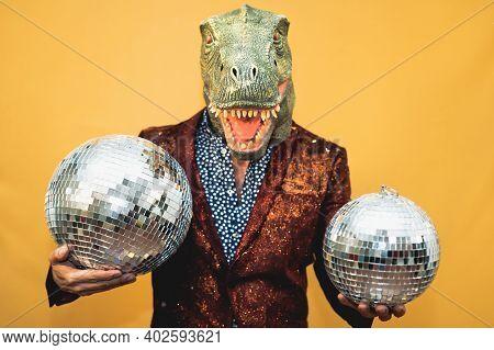 Fashion Senior Man Wearing T-rex Dinosaur Mask While Celebrating Carnival Holidays - Surreal Masking