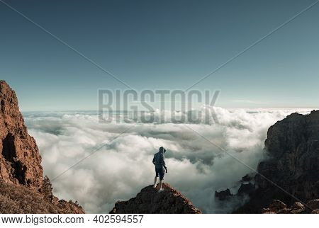 Man Standing On The Mountain Peak Above The Clouds