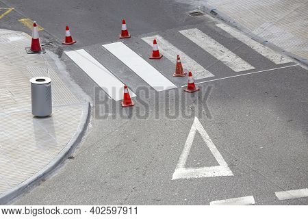 Road Painting Maintenance Concept. Painting White Street Lines On Pedestrian Crossing And Road Cones