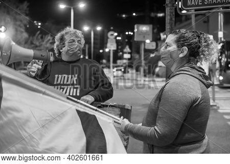 Haifa, Israel - January 09, 2021: Protestors With Flag And Megaphone Take Part In The Black Flags Pr