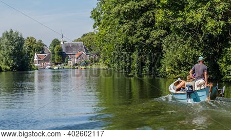 Zuilen, Netherlands - August 25, 2018: Boating On The River Vecht Along The Church Of Zuilen Near Ut