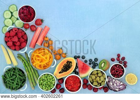 Healthy vegan plant based fruit and vegetables super food background border high in antioxidants, fibre, anthocyanins, vitamins, minerals, protein, carotenoids and smart carbs. On mottled blue.