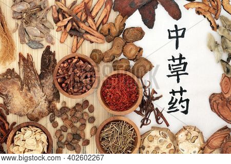Traditional Chinese herbal medicine with herbs and calligraphy script on rice paper and bamboo. Holistic health care concept. Flat lay, top view. Translation reads as Chinese healing herbs.