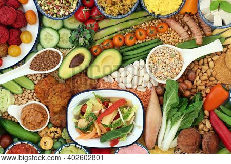 Vegan food for a healthy immune boosting diet with legumes, vegetables, nuts, dips, grains, snacks and cereal products. Plant based health foods for ethical eating and a healthy planet. Flat lay.
