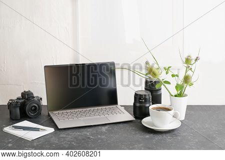 Office Workspace Of A Photographer Designer, Gray Desk With Laptop, Camera, Lenses And A Coffee Cup