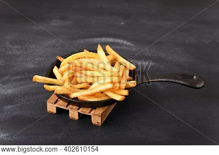 Fried Fries In A Frying Pan On A Wooden Pallet Trivet.