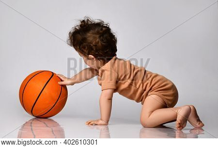 Games For Children. Playful Curly Kid In A Brown Bodysuit Plays Basketball With Interest On A Gray B