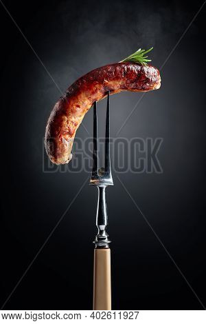 Grilled Bavarian Sausage With Rosemary On A Fork.