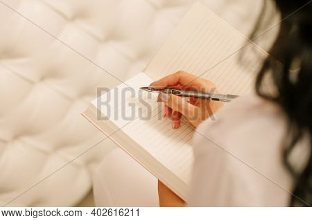Female Woman Hand Holding Notepad And Writing With Pen. Pencil On Paper, Metal Parker. Light Backgro