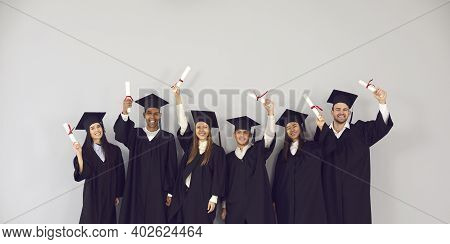 Group Of Happy Multiethnic College Or University Graduates Holding Up Their Diplomas