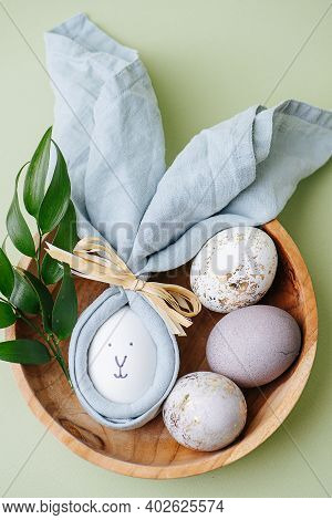Easter Egg In A Napkin Along With Gilded Eggs In A Wooden Bowl