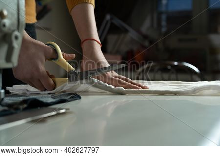 Womens Hands Cut Fabric On A Pattern With Tailors Scissors On A White Table. A Dressmaker At Work In