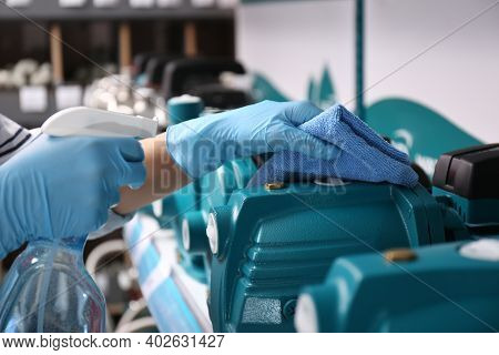 Woman Cleaning Water Pump With Rag And Detergent In Bathroom Fixtures Store, Closeup