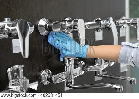 Woman Cleaning Faucets With Rag In Bathroom Fixtures Store, Closeup