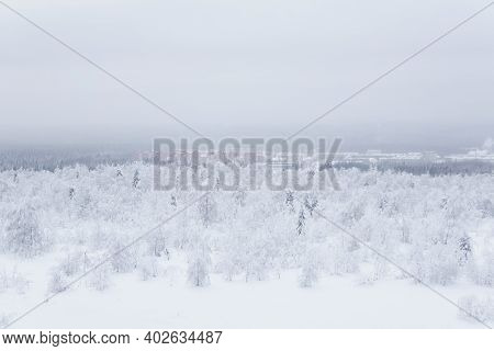 Winter Landscape - A Distant Town In A Valley In The Middle Of Snow-covered Forests In A Frosty Haze