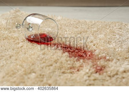 Overturned Glass And Spilled Red Wine On Soft Carpet, Closeup