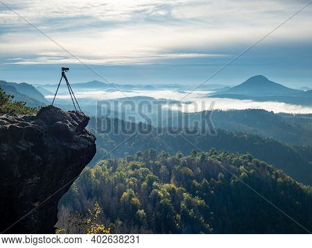 Camera On Tripod Photographing Foggy Mountains, Blue Sky And Foggy Landscape. Mountains Background.