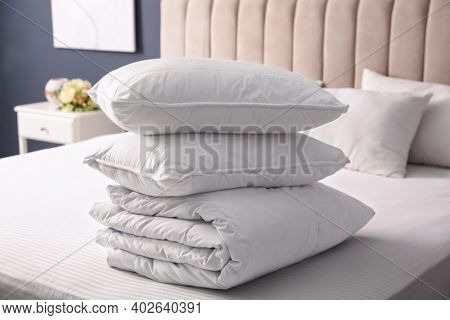 Soft Folded Blanket And Pillows On Bed Indoors